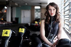 Woman car racer in leather suit holding a helmet Royalty Free Stock Image