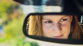 Woman in a Car - Rear View Mirror Royalty Free Stock Photo