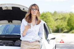Woman with car on the road. Portrait of attractive mature woman standing at her broken down car and using her mobile phone while waiting for emergency assistance Royalty Free Stock Images