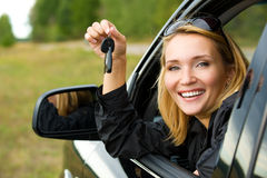 Woman in car showing the keys. Beautiful young happy woman in car showing the keys - outdoors stock photo