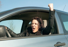 Woman in the car shows the fist Royalty Free Stock Images