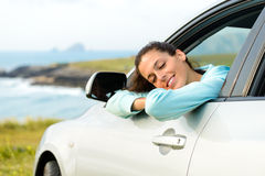 Woman in car on summer travel. Woman in car travel relaxing and enjoying peace and silence of beautiful summer coast nature landscape. Happy girl traveling Royalty Free Stock Photo