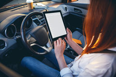 Woman in a car with a tablet in hands Stock Image