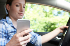 Woman In Car Texting On Mobile Phone Whilst Driving Stock Photography