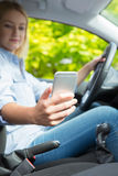 Woman In Car Texting On Mobile Phone Whilst Driving Royalty Free Stock Photos