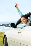 Woman on car travel with keys. Woman driving car and holding keys on summer travel to coast. Happy female driver out of the auto window Stock Images