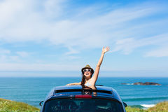 Woman on car vacation travel waving. Joyful woman waving on summer car travel vacation to the coast. Brunette girl having fun leaning out vehicle sunroof towards Royalty Free Stock Photo