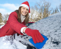 Woman, car, winter. Young woman with Santa Claus outfit scratching windshield of a car stock image