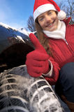 Woman, car, winter. Young woman in Santa Claus outfit with winter tire shows thumbs up royalty free stock photo