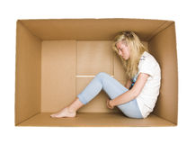 Woman in a cardboard box. Woman siting in a cardboard box isolated on white background Royalty Free Stock Photography