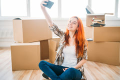 Woman among cardboard boxes makes selfie on camera. Smiling woman sitting on the floor among cardboard boxes and makes selfie on mobile phone camera Royalty Free Stock Photos