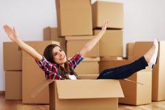 Woman in cardbox. Cheerful woman sitting in a cardboard box Stock Photo