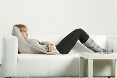 Woman in cardigan relaxed on sofa Stock Photography
