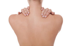 Woman caressing her bare shoulder and back. Woman standing facing away caressing her bare shoulder and tanned toned back with her fingers in a sensual portrait Royalty Free Stock Photo