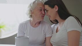 Woman caressing and hugging grandmother.