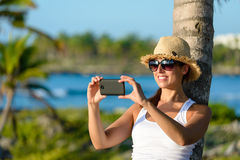 Woman on caribbean travel taking photo with smartphone Royalty Free Stock Photos