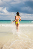 Woman on caribbean vacation running to the sea splashing Stock Image