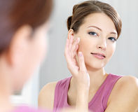 Woman caring of her beautiful skin on the face. Standing near mirror in the bathroom royalty free stock image