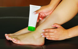 Woman caring about her feet and putting hydrating cream on it with cream bottle.  Stock Photo