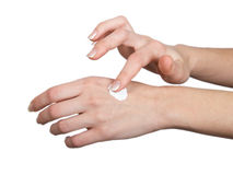 Woman caring for her hands. The woman rubs to itself in a hand cosmetic means for a white background Stock Photos