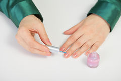 Woman caring for nails - paints with nail polish Stock Image