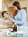 Woman caring for sick guy who high temperature royalty free stock photography