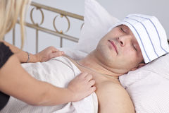 Woman caring for sick man stock image