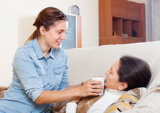 Woman caring for sick mature mother at home stock images