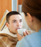 Woman caring for unwell man Royalty Free Stock Image