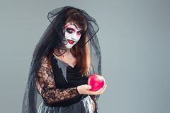 Woman in a carnival costume of a witch or a dead bride holding a. N apple in her hands, gothic woman in witch costume on gray background, halloween portrait of stock photos