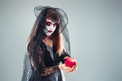 Woman in a carnival costume of a witch or a dead bride holding a. N apple in her hands, gothic woman in witch costume on gray background, halloween portrait of royalty free stock image