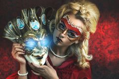 Woman with Carnival Mask Ball. Portrait of beautiful young girl with creative make up and big carnival mask in her hands, blonde hairstyle. Louis court intrigues Royalty Free Stock Photography
