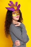 Woman in carnival mask with feather, beautiful girl portrait on yellow color background, long curly hair Royalty Free Stock Image