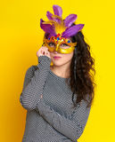 Woman in carnival masquerade mask with feather, beautiful girl portrait on yellow color background, long curly hair Stock Photo