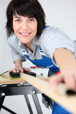Woman carpenter. Portrait of woman carpenter working piece of wood Royalty Free Stock Image