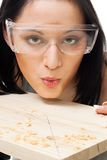 Woman carpenter blow away scobs. From wood, closeup Royalty Free Stock Photos