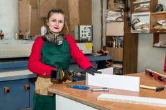 Woman carpenter with drill machine constructing furniture. Woman carpenter with drill machine constructing furniture royalty free stock photo