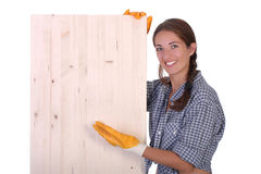 Woman carpenter holding wooden plank Royalty Free Stock Image
