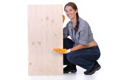 Woman carpenter holding wooden plank Royalty Free Stock Photography
