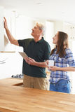 Woman With Carpenter Inspecting New Fitted Kitchen Stock Images