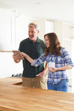 Woman With Carpenter Looking At Plans For Kitchen On Digital Tab Royalty Free Stock Image