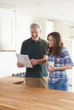 Woman With Carpenter Looking At Plans For New Kitchen royalty free stock image