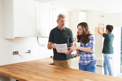 Woman With Carpenter Looking At Plans For New Kitchen Stock Images