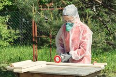 Woman carpenter in respirator, goggles and overalls handles a wooden board with a Angle grinder stock images