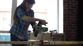 Woman carpenter saws wooden bar using circular electric saw in workshop. The process of building a wooden table, a woman carpenter saws a wooden bar using a stock video