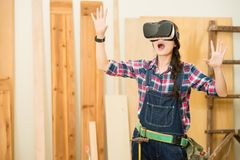 Woman carpenter shocked  looking vr device Royalty Free Stock Image