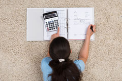 Woman On Carpet Calculating Finance Royalty Free Stock Photo