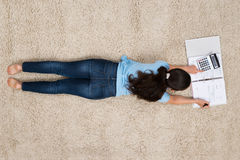 Woman On Carpet Calculating Finance Stock Photography