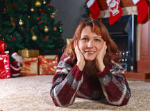 Woman on the carpet in the room with fireplace and Christmas dec Royalty Free Stock Photography