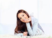 Woman on carpet taking notes. Young smiled woman on carpet at home with notepad and pen Stock Images